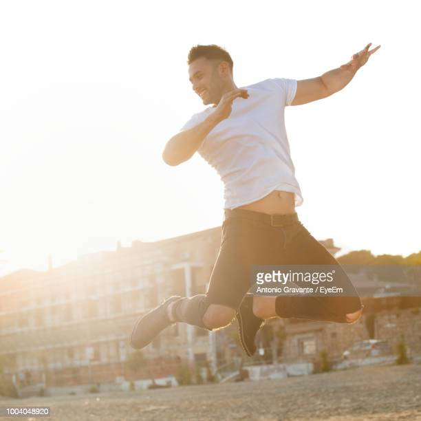 Full Length Of Young Man Jumping In City Against Clear Sky