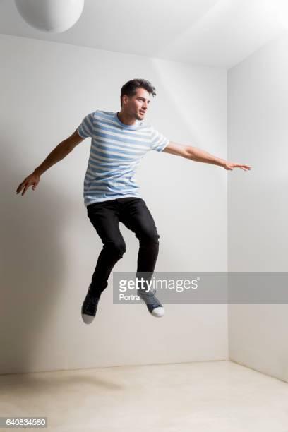 Toute la longueur du jeune homme sautant dans la chambre