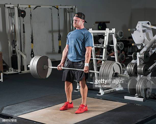 full length of young man lifting barbell in gym - struggle stock pictures, royalty-free photos & images