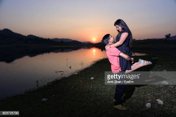 Full Length Of Young Man Lifting Woman While Standing On Grass Field By Lake Against Sky During Sunset