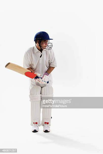 Full length of young man playing cricket over white background
