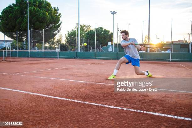 full length of young man playing tennis on field - tênis esporte de raquete - fotografias e filmes do acervo