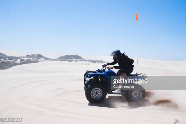 full length of young man riding quadbike at pismo beach against clear sky during sunny day - ピスモビーチ ストックフォトと画像