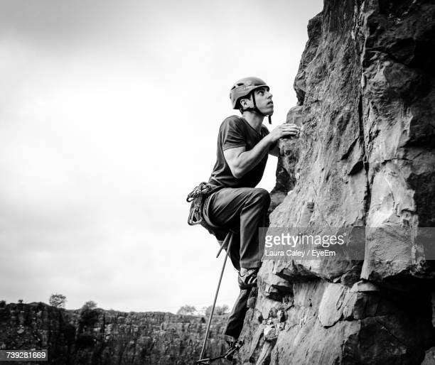 Full Length Of Young Man Rock Climbing Against Sky