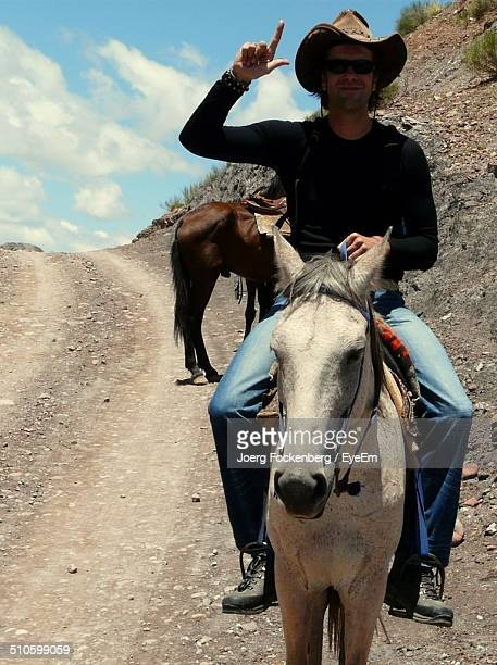 Full length of young man showing loser sign while riding horse in desert trail