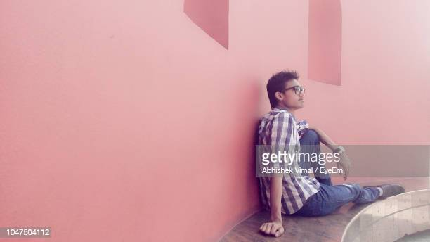Full Length Of Young Man Sitting By Wall