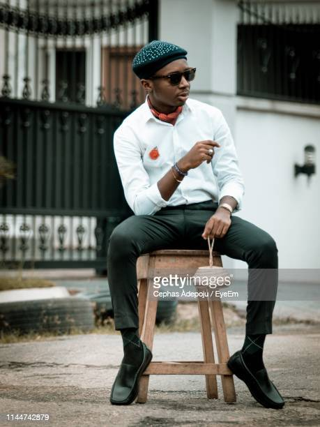 full length of young man sitting on stool - lagos nigeria fotografías e imágenes de stock
