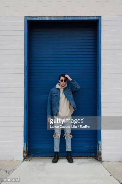 full length of young man standing against blue door - blue jacket stock pictures, royalty-free photos & images