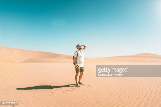 full length of young man standing in desert against clear sky - 砂漠 ストックフォトと画像