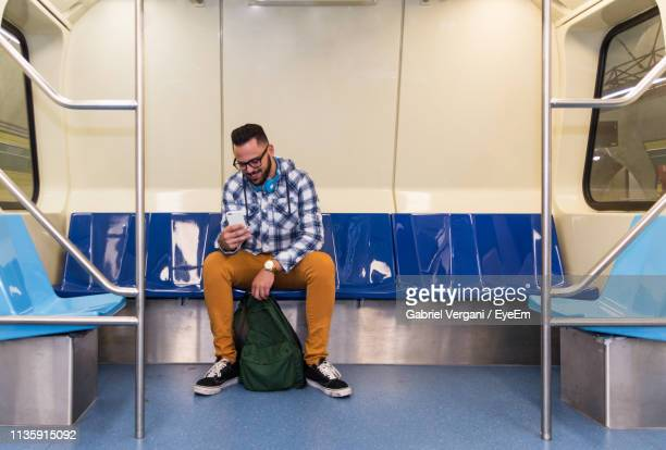 full length of young man using mobile phone while sitting in train - 地下鉄 ストックフォトと画像