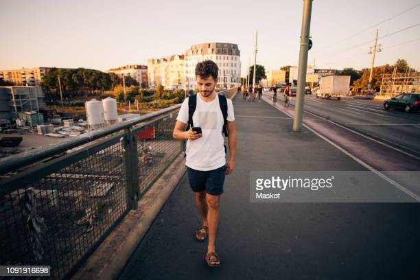full length of young man using mobile phone while walking on footpath at bridge in city - mensch im hintergrund stock-fotos und bilder