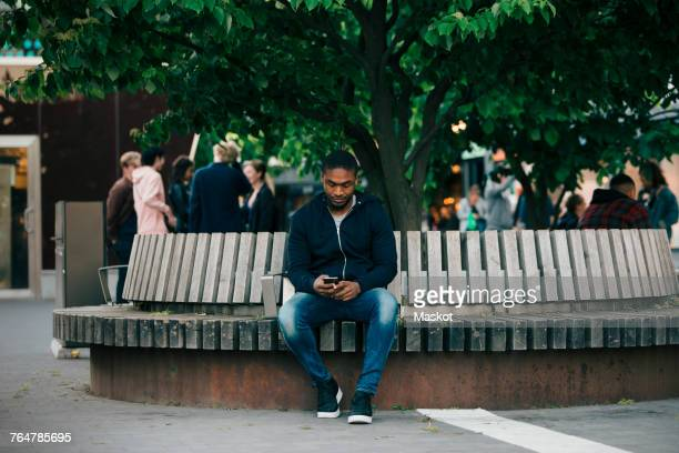 Full length of young man using smart phone while sitting on bench in city