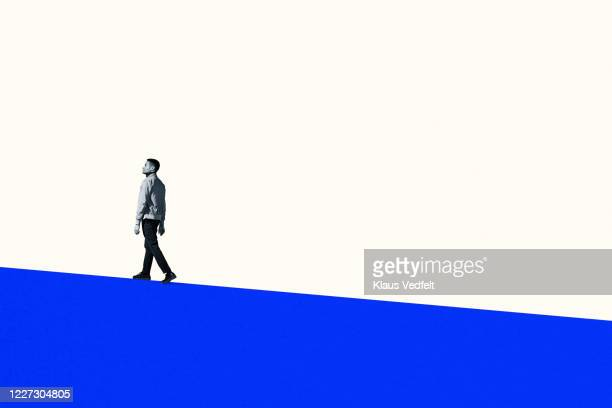 full length of young man walking on blue hill - moving up stock pictures, royalty-free photos & images