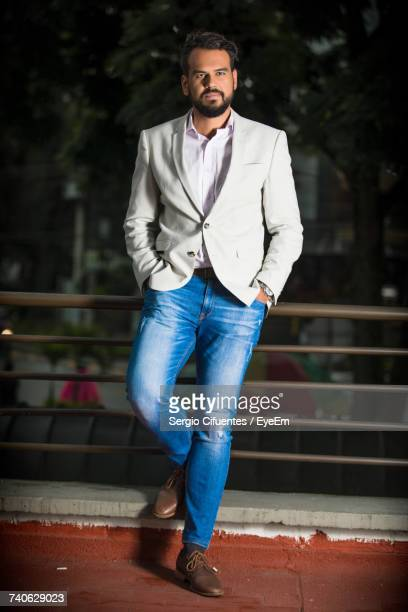 full length of young man wearing blazer in balcony - blazer jacket stock pictures, royalty-free photos & images