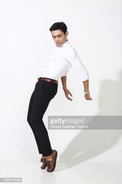 full length of young man wearing formalwear against white background - ダンス ストックフォトと画像