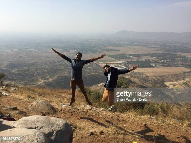 Full Length Of Young Men Jumping On Mountain Against Landscape