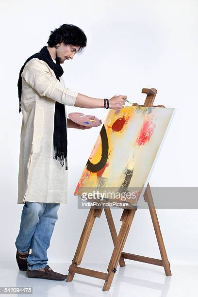 Full length of young painter painting against white background