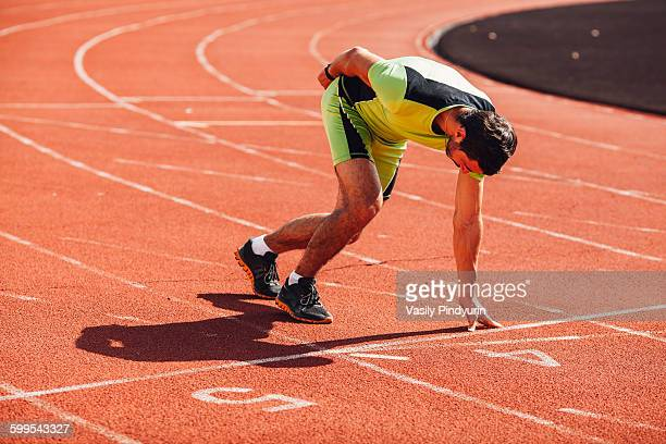 Full length of young runner at starting block on track