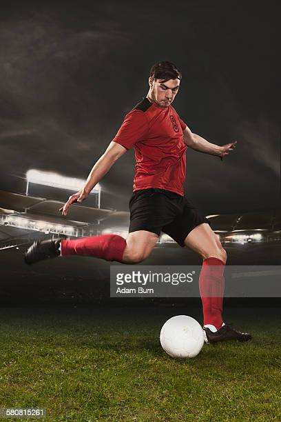 Full length of young soccer player kicking ball on field