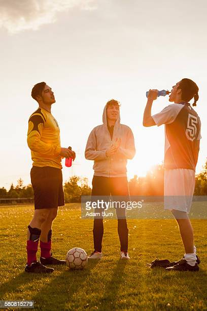 full length of young soccer players standing on field - 冷たい飲み物 ストックフォトと画像