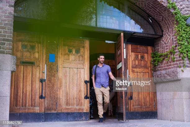 full length of young student leaving language school - partire foto e immagini stock