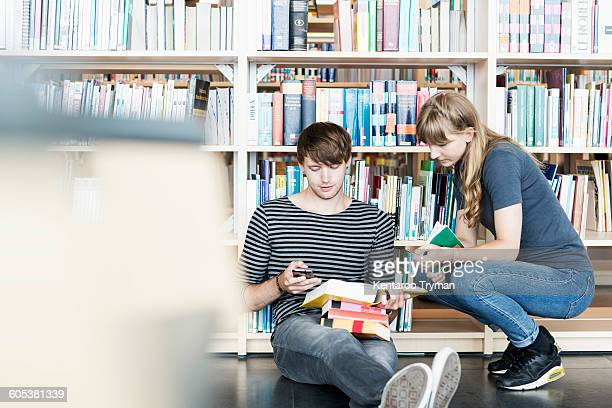 Full length of young students with books using mobile phone in college library