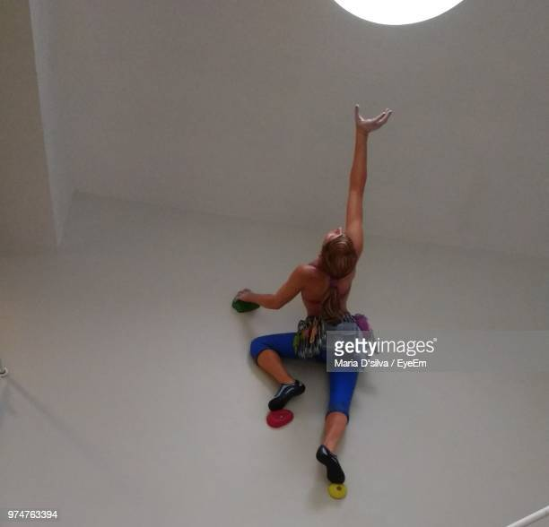 full length of young woman climbing on wall - pursuit concept stock photos and pictures