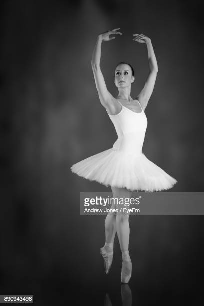 Full Length Of Young Woman Dancing Against Black Background