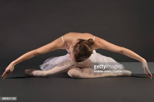 Full Length Of Young Woman Dancing Against Gray Background