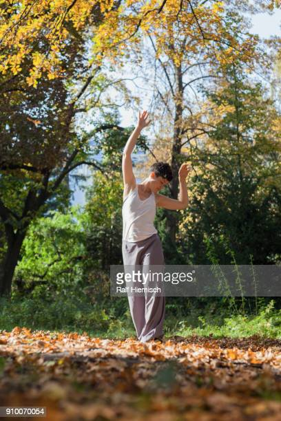 Full length of young woman dancing on field against plants at park during autumn