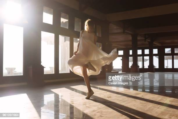 full length of young woman dancing on tiled floor during sunny day - standing on one leg stock pictures, royalty-free photos & images