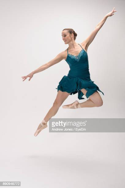 Full Length Of Young Woman Dancing On White Background