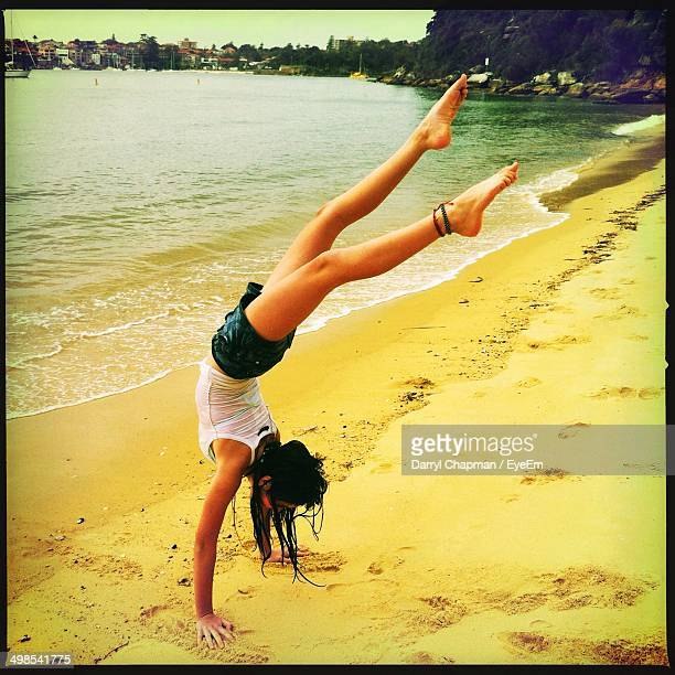 Full length of young woman doing handstand on beach