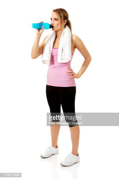 full length of young woman drinking water against white background - durst stock-fotos und bilder