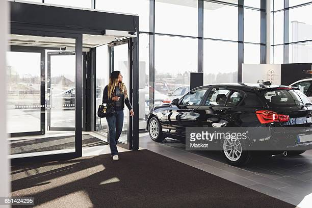 full length of young woman entering car showroom - car dealership stock pictures, royalty-free photos & images