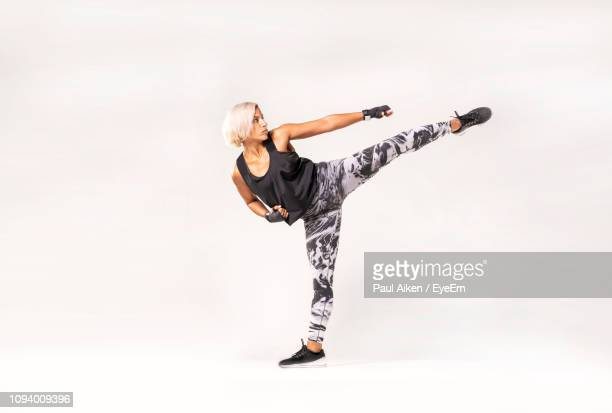 full length of young woman exercising against white background - kicking ストックフォトと画像