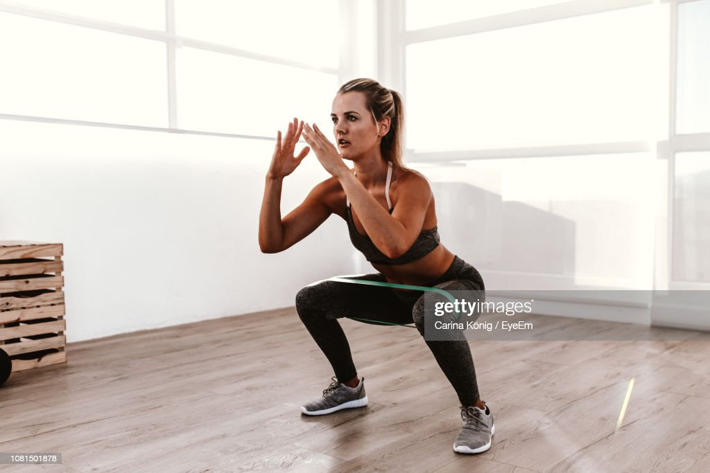 Full Length Of Young Woman Exercising In Gym : Stock Photo