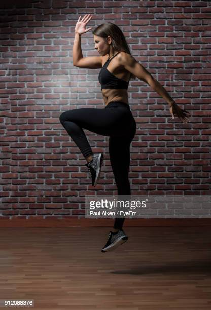 full length of young woman exercising in gym - aikāne stock pictures, royalty-free photos & images