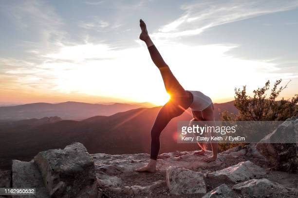 full length of young woman exercising on rock against sky - kerry estey keith stock photos and pictures