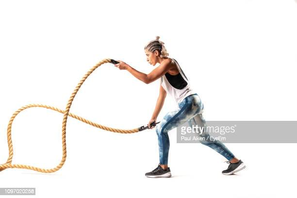 full length of young woman exercising with ropes against white background - aikāne stock pictures, royalty-free photos & images