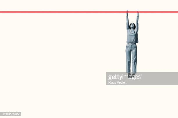 full length of young woman hanging from red rope - hanging stock pictures, royalty-free photos & images