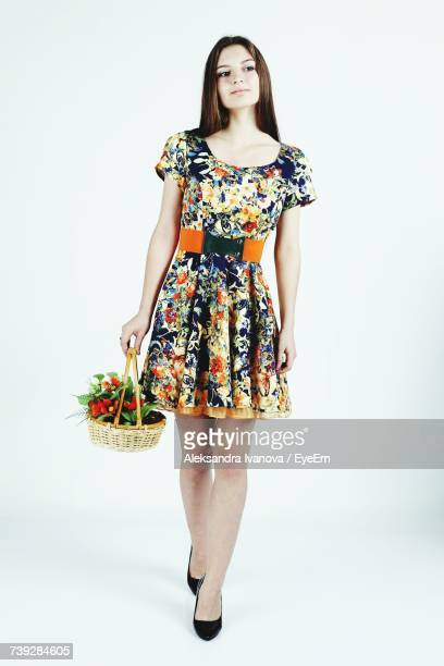 full length of young woman holding flower basket while walking against white background - vestido de colores fotografías e imágenes de stock