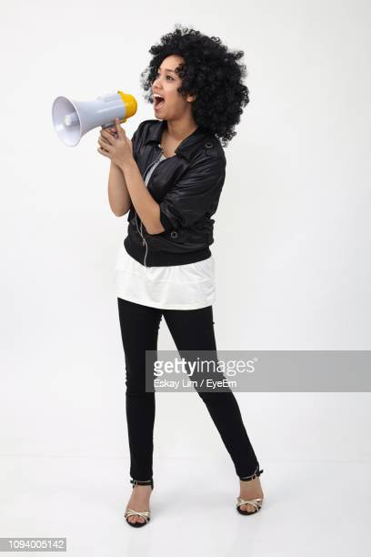 full length of young woman holding megaphone on white background - megaphone stock pictures, royalty-free photos & images