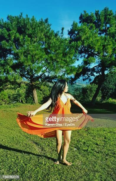 Full Length Of Young Woman Holding Orange Dress While Standing On Field