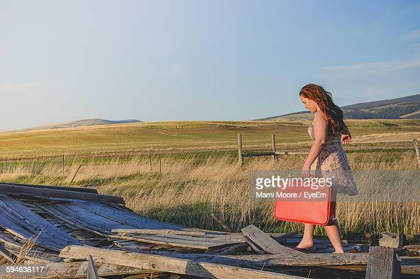 Full Length Of Young Woman Holding Red Suitcase While Walking On Abandoned Wood Against Sky