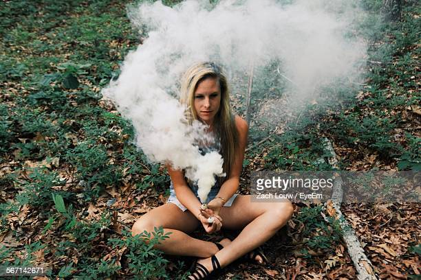Full Length Of Young Woman Holding Smoke Bomb While Smoke Emitting From It