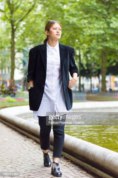 full length of young woman in blazer by pond on footpath at park - hands in pockets stock pictures, royalty-free photos & images
