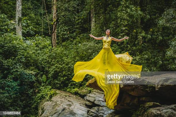 full length of young woman in long yellow dress standing on cliff in forest - robe longue photos et images de collection