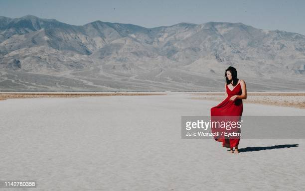 full length of young woman in red dress standing on sand dune against mountain during sunny day - red dress stock pictures, royalty-free photos & images