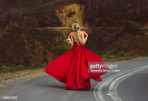 full length of young woman in red evening gown walking on road - ロングドレス ストックフォトと画像
